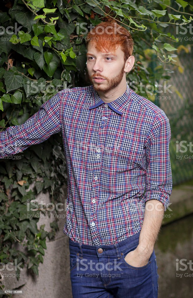Fashionable red haired model posing outdoors. stock photo