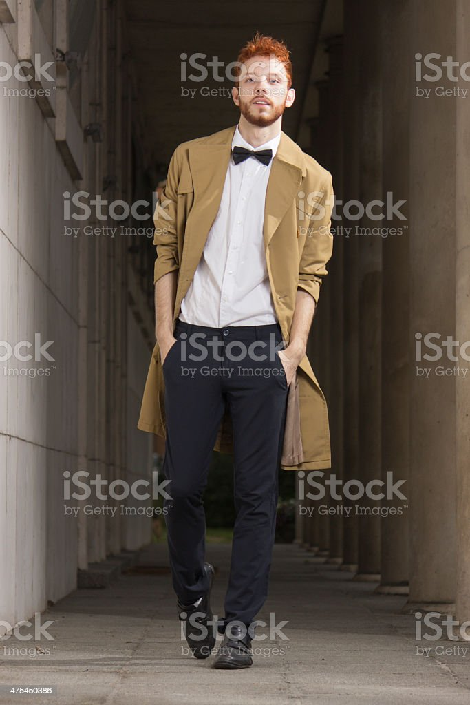 Fashionable red haired model posing outdoors, walking, full body shot. stock photo