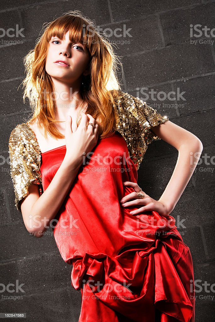 Fashionable red-haired woman in a satin red dress stock photo