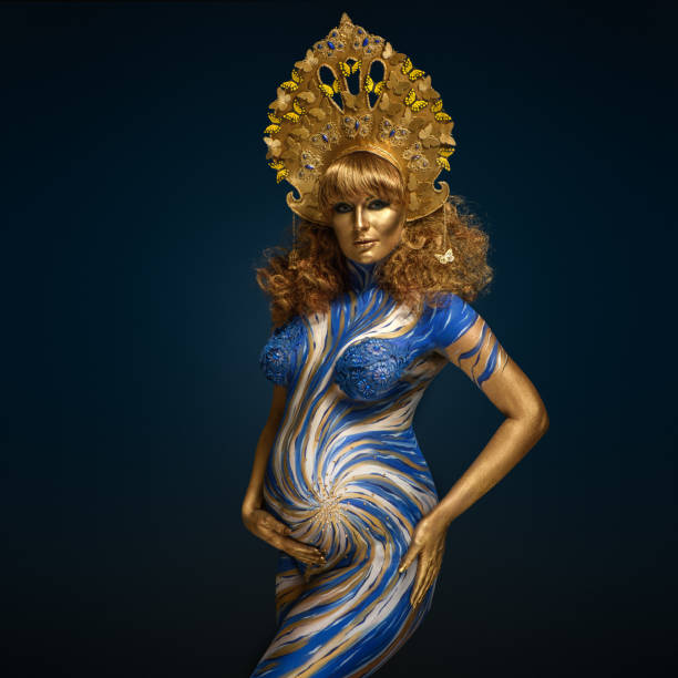 fashionable redhead pregnant woman with kokoshnik and abstract body art in shades of blue and gold - makeup for pregnant women stock photos and pictures