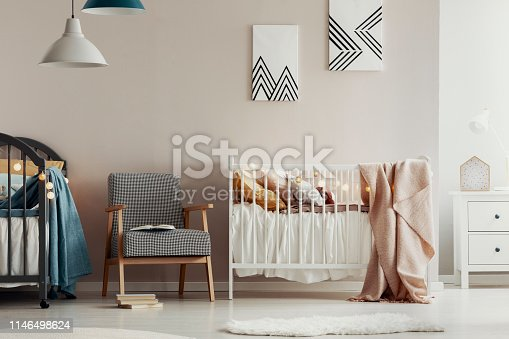 istock Fashionable retro armchair between two wooden cribs in cute twins nursery 1146498624
