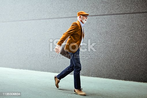 Fashionable Senior Man Outdoors wearing laptop bag