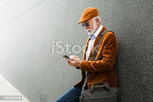 Fashionable Senior Man Outdoors using smart phone