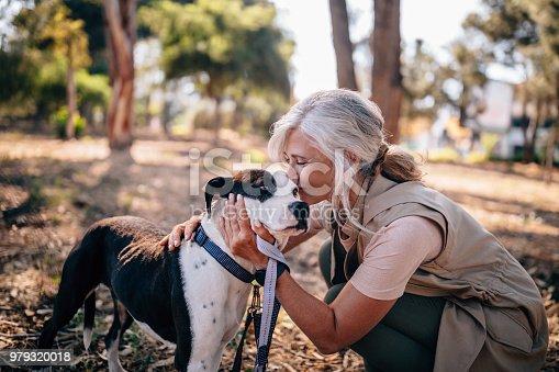 istock Fashionable senior woman kissing pet dog in nature 979320018