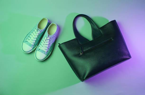 modische sneakers, handtasche neongrünes lila licht. retro-stil 80er jahre, minimalismus - neontasche stock-fotos und bilder