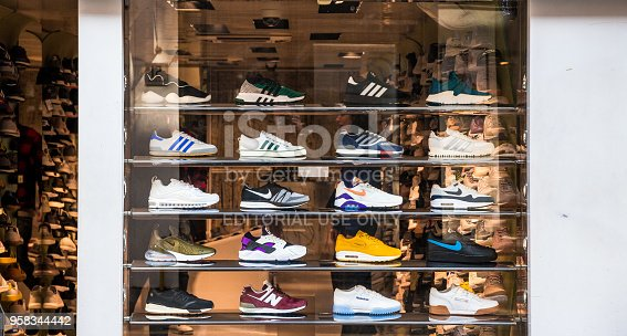 London, UK - 21 March, 2018: retail display of trendy sneakers displayed in the window of a shoe shop in central London, UK. The sneakers are displayed neatly in a row, and include brands such as Adidas, New Balance and Nike. Room for copy space.