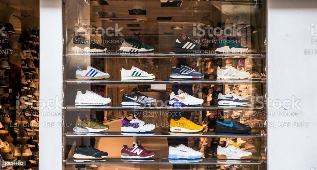 Fashionable sneakers on display in shop window, London, UK stock photo