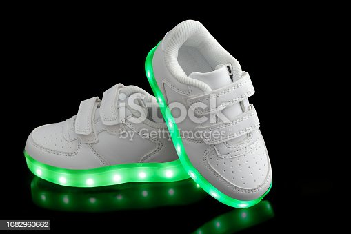 Fashionable sneakers with LED lighting on black backgrounds