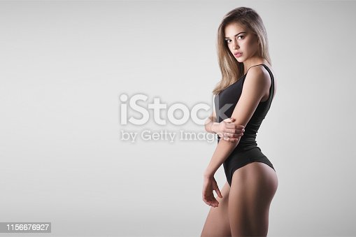 young model with a perfect body. Model with a sports figure in lingerie. Stylish portrait of a pretty girl with clean skin. Studio portrait of a young girl on a gray background. Advertising space