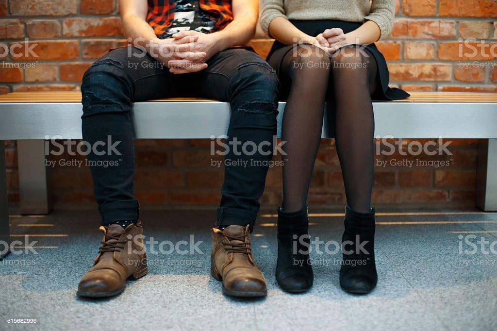 Fashionable stylish couple sitting on the bench. Legs close-up stock photo