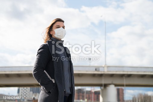 Fashionable stylish scared woman in protective blue face mask, gray wool coat on the street near metro station. Windy day. Self protection in transport during quarantine from coronavirus covid-2019.
