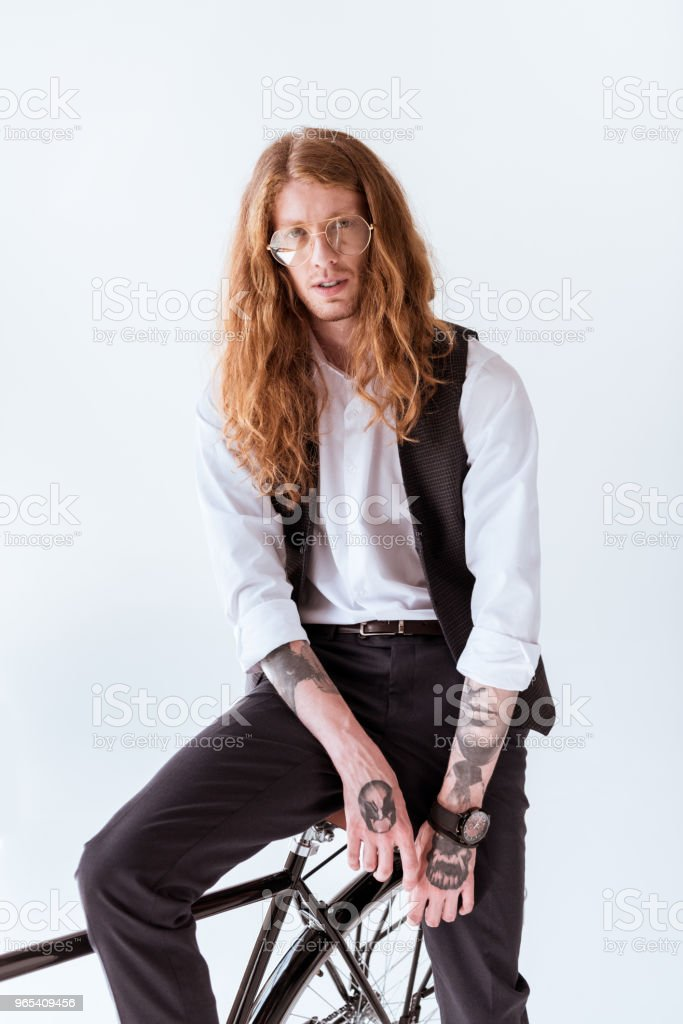 fashionable tattooed businessman with curly hair sitting on bicycle isolated on white zbiór zdjęć royalty-free