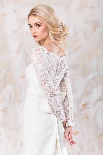 modisches weißes kleid, schöne blonde model, braut-frisur und make-up-konzept - junge charmante dame im hochzeit festliche kleid stehen im innenbereich auf hellem hintergrund, hübsche frau posiert - festliche kleider kindermode stock-fotos und bilder