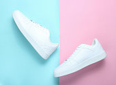 Fashionable white sneakers on a colored pastel background, minimalism, top view, creative layout, step