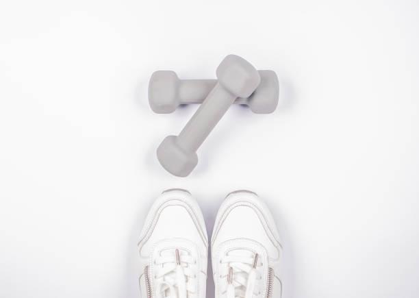 Modischer weißer Sport Sneacker mit Hantel isoliert auf Weiß – Foto