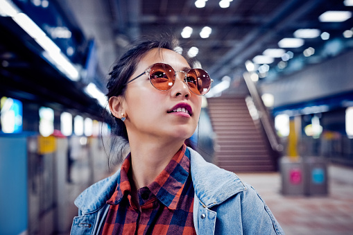 Smiling fashionable woman looking away. Young female is at subway station. She is on city break.