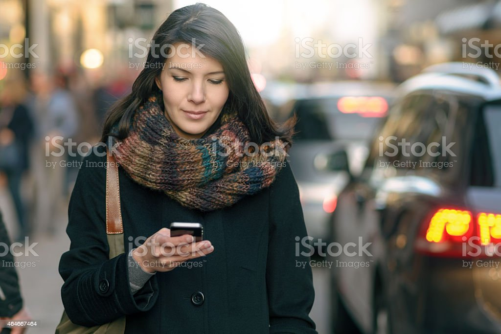 Fashionable Woman Busy with Phone at City Street stock photo