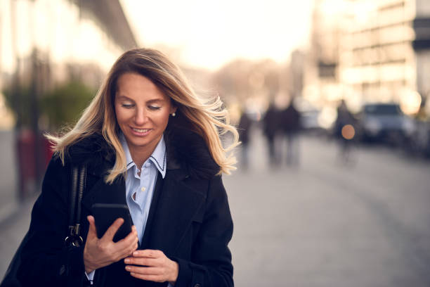 fashionable woman busy with phone at city street - older woman phone stock photos and pictures