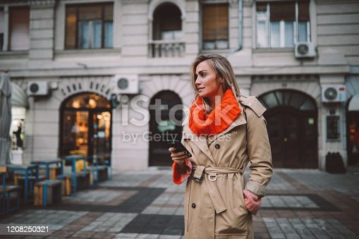 Portrait of a fashionable woman in her 30s, checking apps on her mobile phone, texting or just calling a cab.