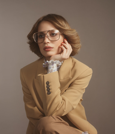 Portrait of beautiful fashionable woman wearing eyeglasses and beige suit, 70s style