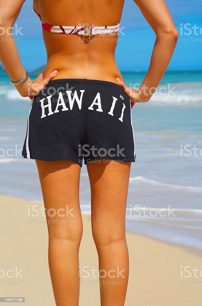 Fashionable woman in bikini and shorts on the beach royalty-free stock photo