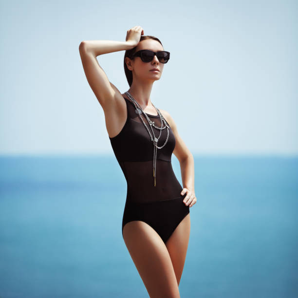fashionable woman in black swimsuit - beach fashion stock photos and pictures