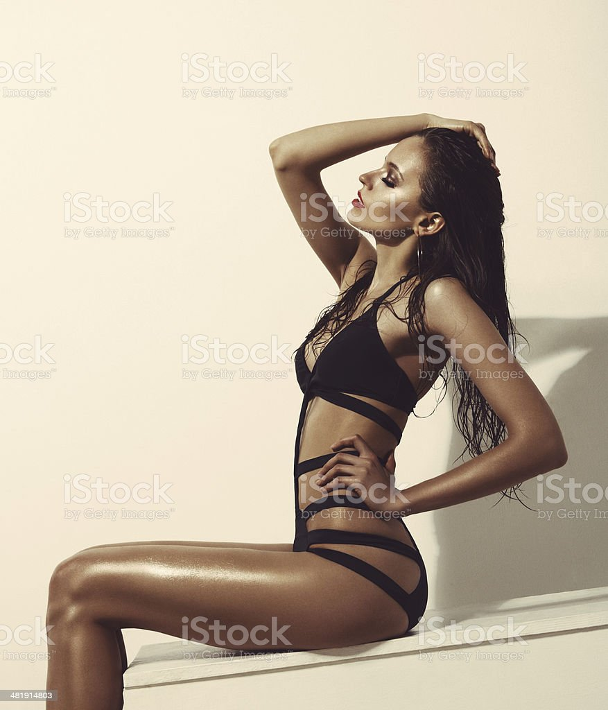 Fashionable woman in black swimsuit stock photo