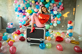 istock Fashionable woman in high heels sitting on box with balloon in hand 1187650974
