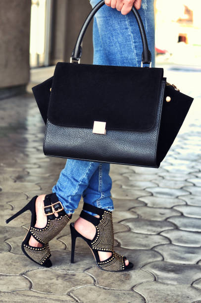 Fashionable woman in jeans wearing black high heels sandals with rivets holding black leather bag, walking on the street stock photo
