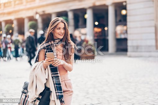 Fashionable woman holding phone and walking on the street