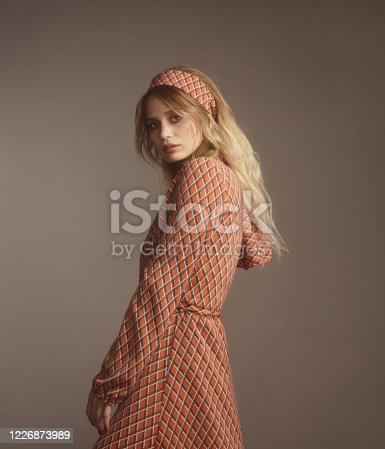 Portrait of beautiful fashionable woman wearing print dress, 70s style