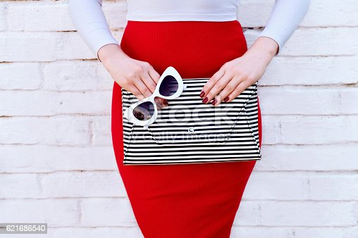 istock Fashionable woman in red skirt with striped clutch 621686540