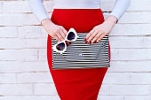 Fashionable woman in red skirt with striped clutch