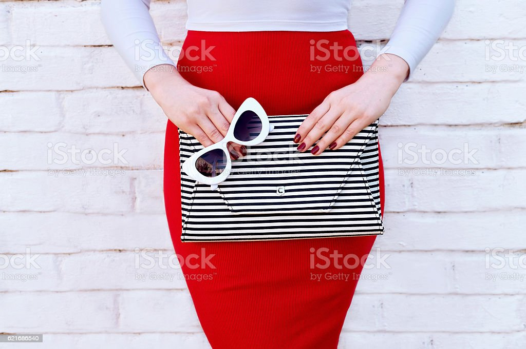 Fashionable woman in red skirt with striped clutch stock photo