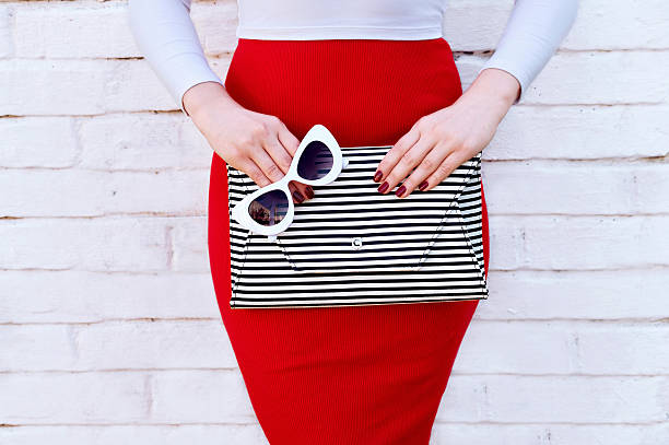 Fashionable woman in red skirt with striped clutch - Photo