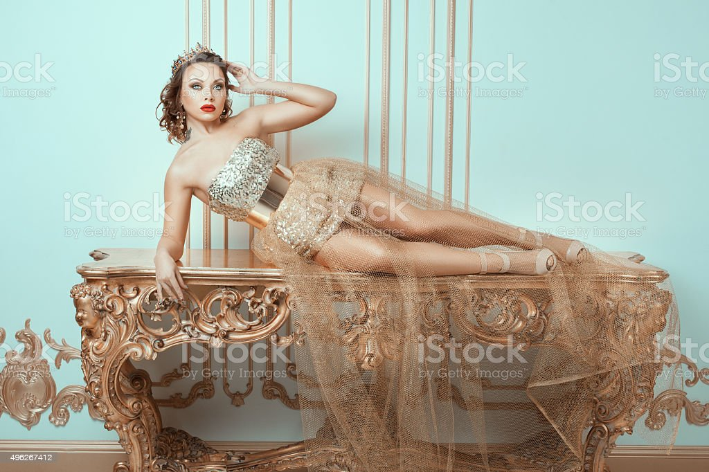 Fashionable woman lies on an expensive antique table. stock photo