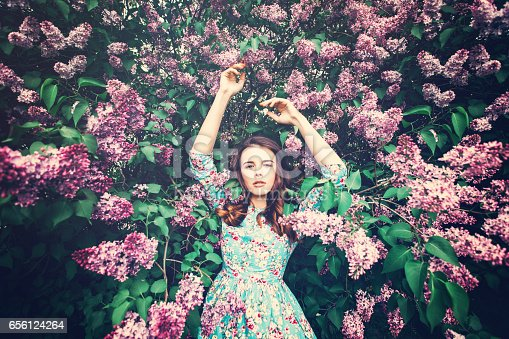 istock Fashionable Woman on Floral Blossom Background 656124264