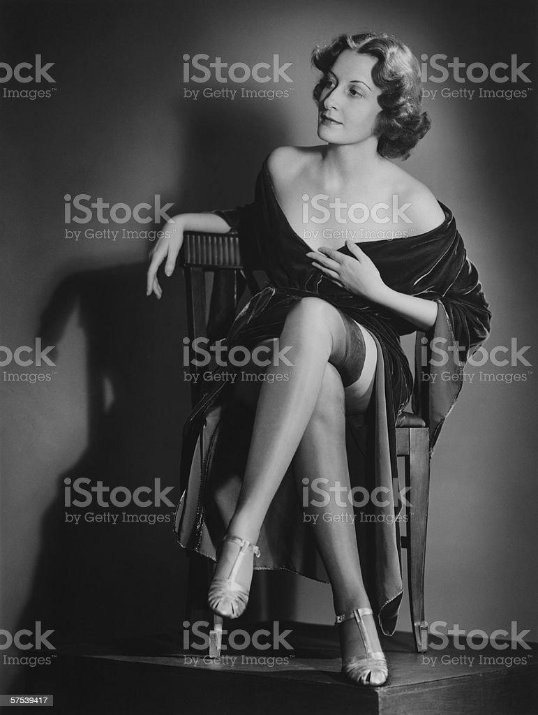 Fashionable woman posing in studio, showing legs, (B&W), portrait stock photo
