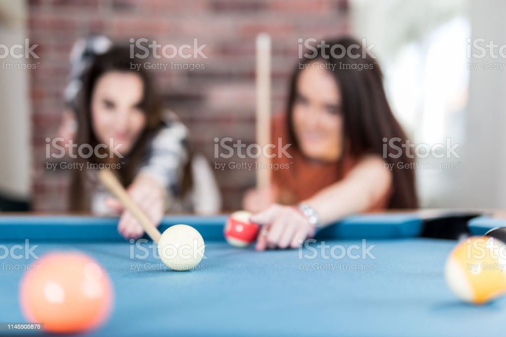 Couple of female friends enjoying the pool table billiard game.