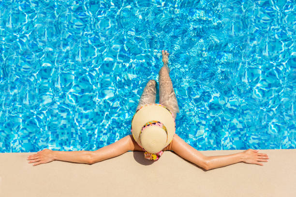 Fashionable woman relaxing in a swimming pool stock photo