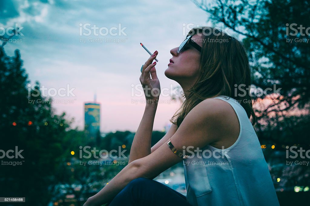 Fashionable woman smoking cigarette outdoors. stock photo