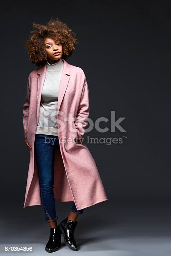 Fashionable young woman standing against gray background. Portrait of attractive female with hands in pockets. She is wearing long coat.