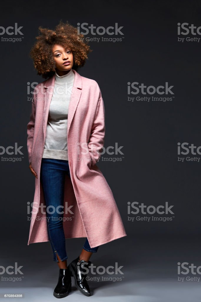 Fashionable woman standing against gray background stock photo