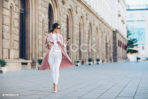 istock Fashionable woman texting outdoors 619265078