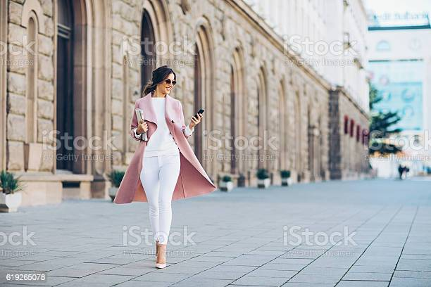 Elegant young woman walking on the square and texting in urban environment.