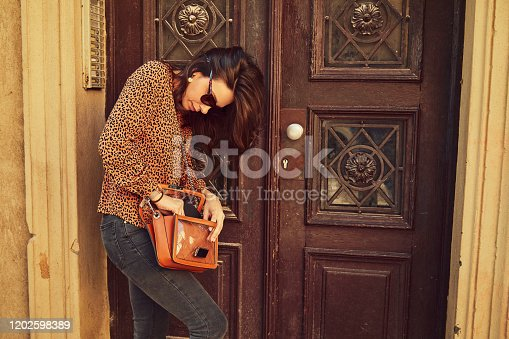 Fashionable woman tries to find the key for apartment.
