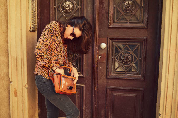 Fashionable woman tries to find the key for apartment. stock photo