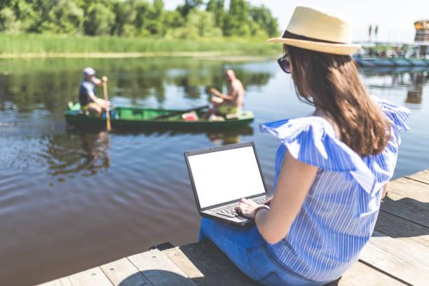 Mujer de moda usando portátil mientras está sentado en el muelle. Personas en barco y hermosa naturaleza en el fondo. - foto de stock
