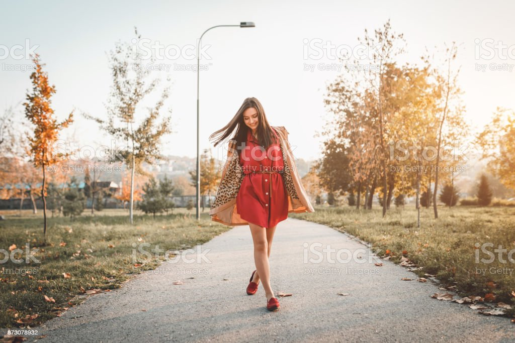 Fashionable woman walking in the public park on a sunny autumn day stock photo