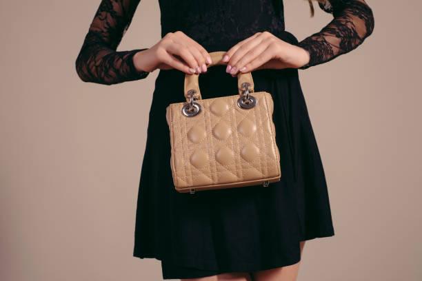 modische frau mit eine braune tasche in ihre hände und schwarzes abendkleid - leder handtaschen damen stock-fotos und bilder